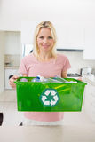 Smiling woman carrying recycling container in the kitchen Stock Images