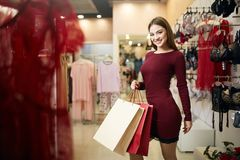 Smiling woman carrying some shopping bags with lingerie store showcase on the background. Pretty smiling caucasian girl. With purhaces in underwear shop Stock Photography