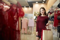 Smiling woman carrying some shopping bags with lingerie store showcase on the background. Pretty smiling caucasian girl. With purhaces in underwear shop Stock Photo