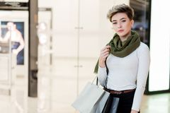 Smiling woman carrying some shopping bags with shops on the background stock images