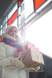 Smiling woman carrying stacked gifts during winter by window Stock Photos