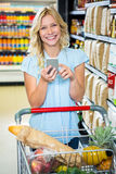 Smiling woman with cart using smartphone Stock Photos