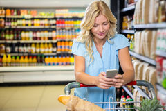 Smiling woman with cart using smartphone Stock Photography