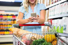Smiling woman with cart using smartphone Stock Image