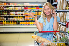 Smiling woman with cart using smartphone Stock Images