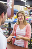 Smiling woman at cash register paying with credit card Royalty Free Stock Image