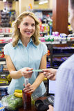 Smiling woman at cash register paying with credit card Royalty Free Stock Images