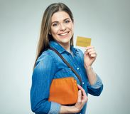 Smiling woman casual dressed shows golden credit card. Royalty Free Stock Photos