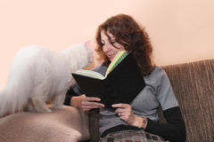Smiling woman and cat reading book Stock Photography