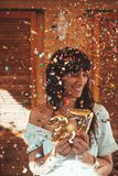 Smiling woman celebrating her 27th birthday with golden numbers and confetti royalty free stock image