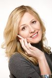 Smiling woman on cell phone. Close up of face of an attractive blond woman holding a pink cell phone over white smiling royalty free stock photography
