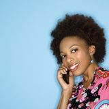 Smiling woman on cellphone. Woman with afro wearing vintage print fabric smiling holding cellphone Royalty Free Stock Photo