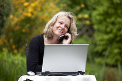 Smiling woman with cellphone and laptop Stock Photos
