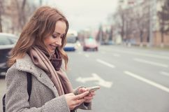 Smiling woman checking email via mobile phone waiting for a bus royalty free stock images