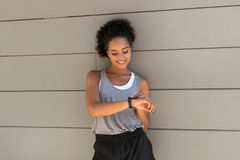 Smiling woman checking pulse. On her fitness tracker Stock Photography