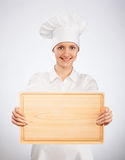 Smiling woman chef cook holding wooden board Stock Photos