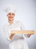 Smiling woman chef cook holding wooden board Royalty Free Stock Image