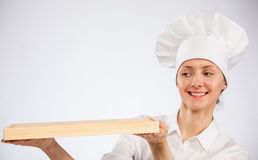 Smiling woman chef cook holding wooden board Stock Photography