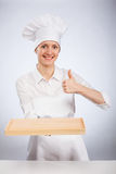 Smiling woman chef cook holding wooden board Stock Photo