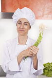 Smiling woman chef with garlic shoots Stock Photos