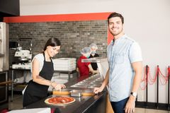 Smiling woman chef smearing tomato ketchup over pizza royalty free stock photo