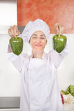 Smiling woman chef with two peppers Stock Images