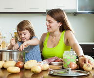 Smiling woman with child cooking Royalty Free Stock Photography