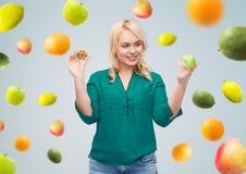 Smiling woman choosing between apple and cookie Royalty Free Stock Image