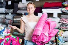 Smiling woman choosing blanket. In bedding section in shop Stock Images