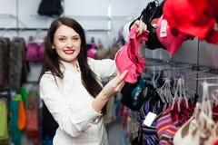 Smiling woman choosing bra at fashion store Royalty Free Stock Images