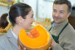 Smiling woman choosing different fruits at farm food store display Royalty Free Stock Photo
