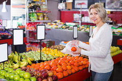 Smiling woman choosing different fruits at store Stock Photo