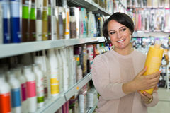 Smiling woman choosing hair care products. In shop and smiling stock image