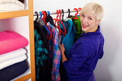 Smiling woman choosing her clothes Royalty Free Stock Photography