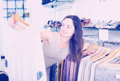 Smiling woman choosing new blouse in apparel shop Royalty Free Stock Photography