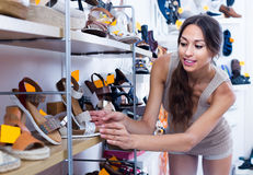 Smiling woman choosing pair of summer shoes Stock Photo