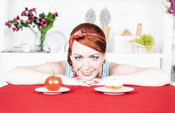 Smiling woman choosing between tomato and cake Royalty Free Stock Images