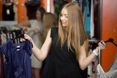 Smiling woman choosing between two garments in shop Stock Images