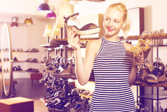 Smiling woman choosing two pairs of new shoes Royalty Free Stock Image