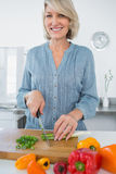 Smiling woman chopping vegetables. At the kitchen counter Stock Photos