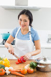 Smiling woman chopping vegetables in kitchen Stock Image