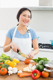 Smiling woman chopping vegetables in kitchen. Smiling young woman chopping vegetables in the kitchen at home Royalty Free Stock Photos
