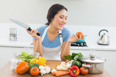 Smiling woman chopping vegetables in kitchen. Smiling young woman chopping vegetables in the kitchen at home Royalty Free Stock Photography