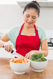 Smiling woman chopping vegetables in kitchen Royalty Free Stock Photos