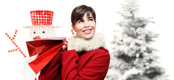 Smiling woman with Christmas gift bag, looks up Royalty Free Stock Images