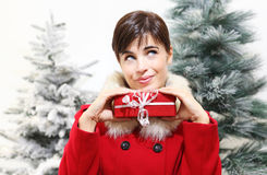 Smiling woman with Christmas gift, looks up, trees in the background Stock Images
