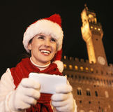 Smiling woman in Christmas hat in Florence, Italy writing sms Stock Photo