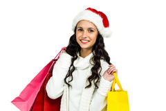 Smiling woman with christmas hat holding colored shopping bags Stock Photo