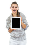 Smiling woman in christmas hat showing tablet pc blank screen