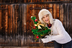 Smiling woman with Christmas tree in front of rustic wood wall Stock Image